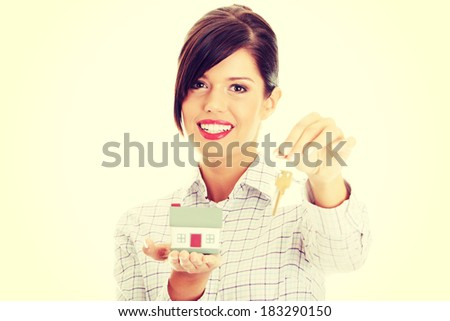 Young businesswoman  (real estate agent) with hose model and keys - stock photo