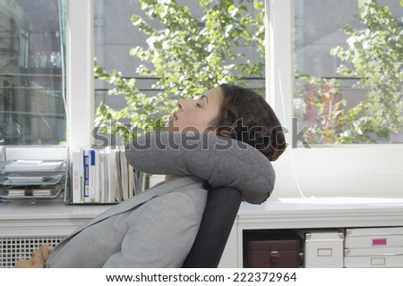 Young businesswoman relaxing at her desk with a neck pillow - stock photo