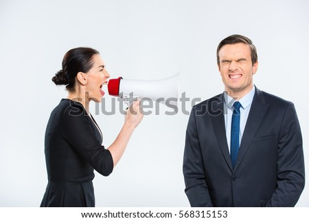 Young businesswoman screaming in megaphone at businessman isolated on white