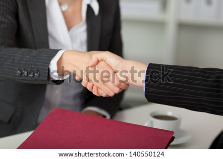 Young businesswoman shaking hands with candidate during an interview at desk - stock photo