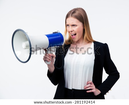 Young businesswoman shouting in megaphone over gray background