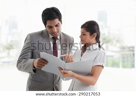 Young businesswoman showing document to businessman in office