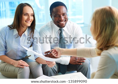 Young businesswoman showing her partners contract at meeting - stock photo