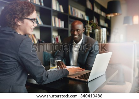 Young businesswoman showing presentation on laptop to her business partner. Happy executives in a meeting at restaurant - stock photo
