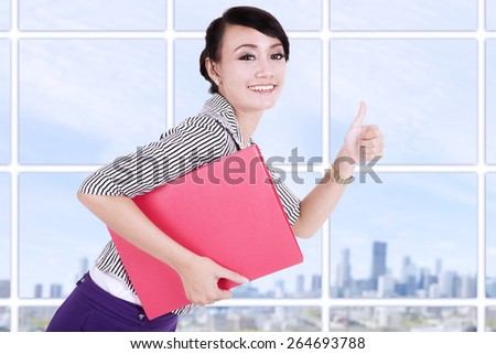 Young businesswoman showing thumb up and holding a folder on modern office - stock photo