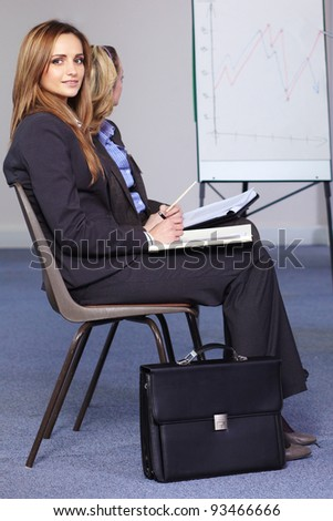 Young businesswoman sits on chair during presentation - stock photo