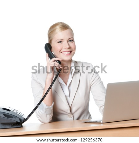 Young businesswoman sitting at a desk and talking by phone, isolated
