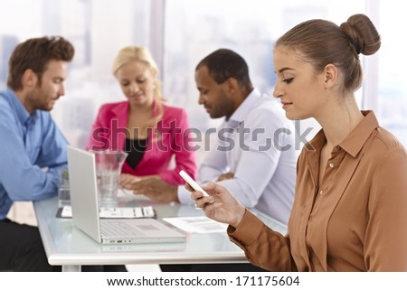 Young businesswoman sitting at a meeting, using mobilephone. - stock photo