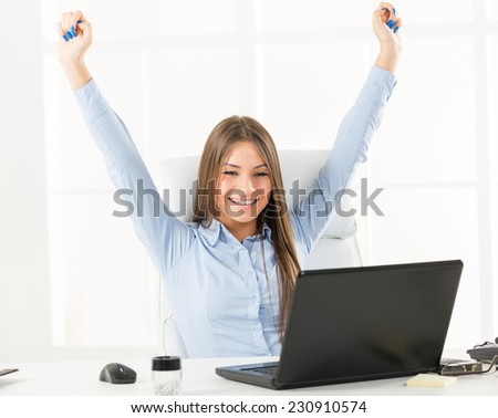 Young businesswoman sitting at an office desk in front of laptop with her hands up, looking forward to business success.
