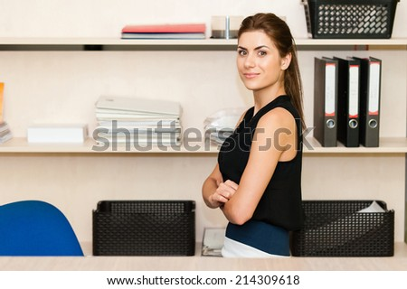 Young businesswoman sitting at desk and working. Smiling and looking at camera - stock photo