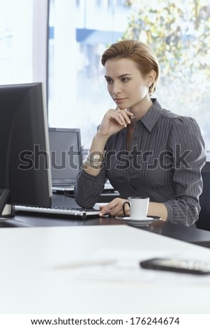 Young businesswoman sitting at desk in bright office, working with computer. - stock photo