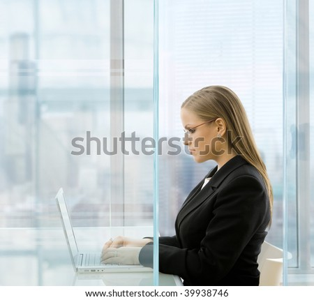Young businesswoman sitting at desk in front of windows in modern office, using laptop computer. - stock photo