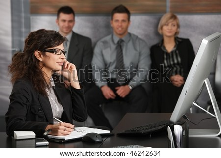 Young businesswoman sitting at desk in office recepcion, talking on mobile phone, smiling, people waiting in background.