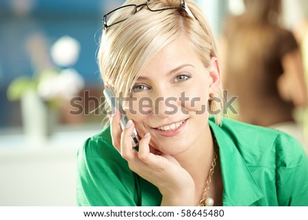 Young businesswoman sitting at desk in office, talking on mobile phone, smiling.