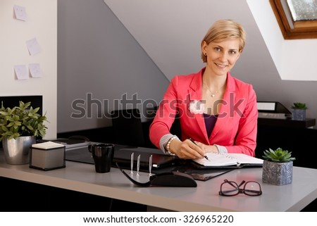 Young businesswoman sitting at desk in office, writing notes to personal organizer, smiling, looking at camera. - stock photo