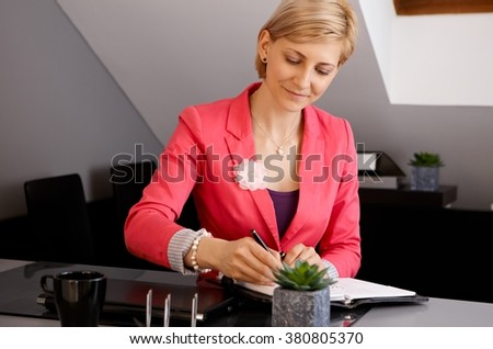 Young businesswoman sitting at desk, writing notes to organizer. - stock photo