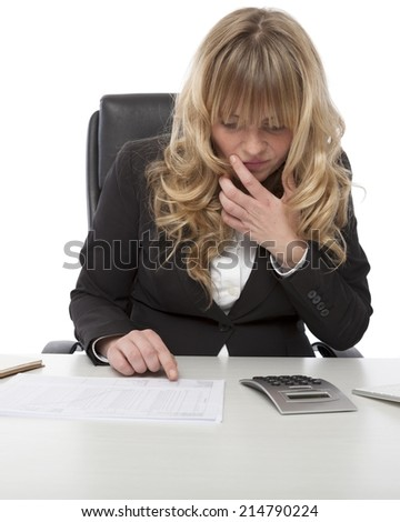 Young businesswoman sitting at her desk checking a written report against her own calculations on a desktop calculator - stock photo