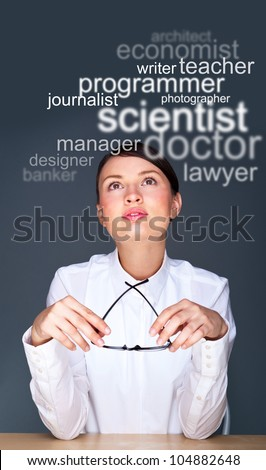 Young businesswoman sitting at her office and thinking about staff she need or about future profession - stock photo
