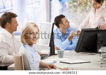 Young businesswoman sitting at office desk, smiling at camera. Others working in the background.