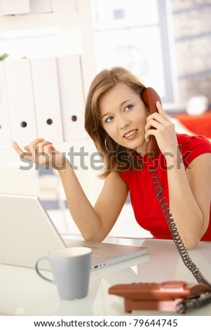 Young businesswoman sitting at office desk, talking on landline phone, gesturing.? - stock photo