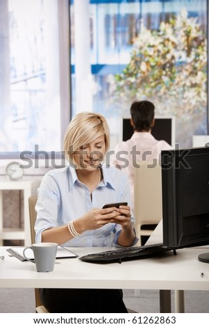 Young businesswoman sitting at office desk, using smart mobile phone.?