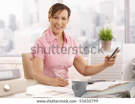 Young businesswoman sitting at office using mobile phone, smiling.