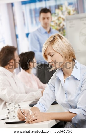 Young businesswoman sitting at table in meeting room writing notes. - stock photo