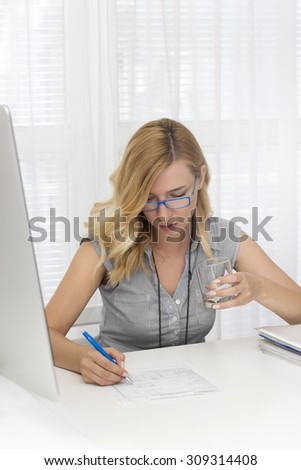 Young  businesswoman  sitting at the desk in the office holding a glass of water and writing. - stock photo