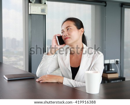 Young businesswoman sitting at the table on workplace in office using the telephone