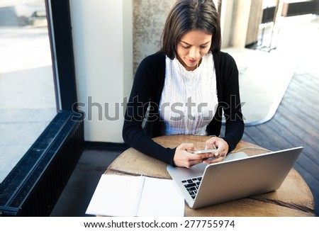 Young businesswoman sitting at the table with laptop and using smartphone in cafe - stock photo