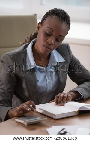 Young businesswoman sitting at workplace and writing numbers in notebook after calculating budget - stock photo