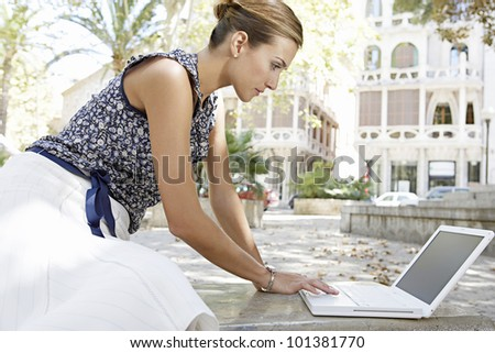 Young businesswoman sitting down and leaning to reach her laptop computer in the city.