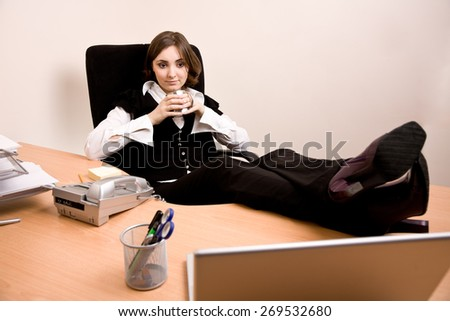 Young businesswoman  sitting in chair and holding a cup of tea at office - stock photo