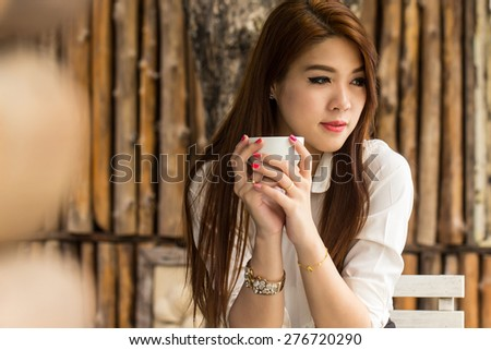 Young businesswoman sitting in coffee shop for check and search internet in the outside. - stock photo