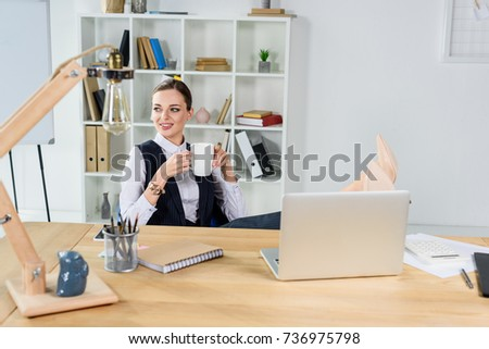 Young businesswoman sitting in office at her desk, holding a cup of coffee
