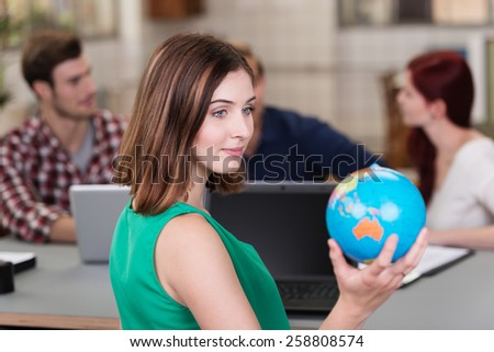 Young businesswoman sitting in the office daydreaming of a vacation holding a globe in her hand as she plans her destinations - stock photo