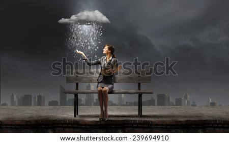 Young businesswoman sitting on bench with book in hands - stock photo