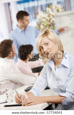Young businesswoman sitting on business meeting in office making notes, looking at camera smiling.? - stock photo