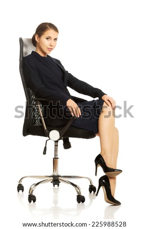 Young businesswoman sitting on chair - stock photo