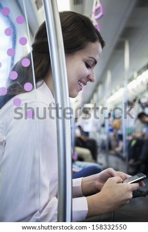 Young businesswoman sitting on the subway and using her phone - stock photo
