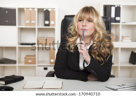 Young businesswoman sitting thinking at her desk as she stares into the distance in deep thought as she tries to come up with a business strategy or solution - stock photo