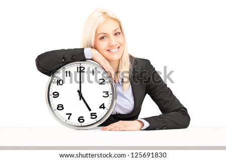 Young businesswoman sitting with a wall clock, isolated on white background