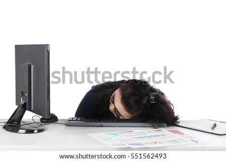 Young businesswoman sleeping on the desk in front of her computer, isolated on white background