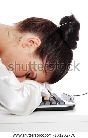 Young businesswoman sleeping on the keyboard in the office. Isolated on white - stock photo