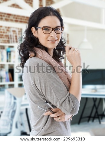 Young businesswoman smiling, holding pens, looking at camera.