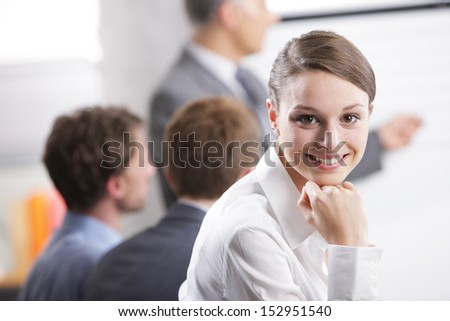 Young businesswoman smiling in a meeting with her colleagues in background - stock photo
