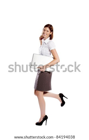Young businesswoman smiling, running and holding notebook under her arm - stock photo