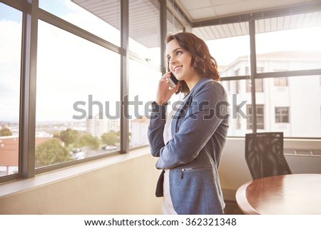 Young businesswoman smiling while listening on her mobile phone and looking out of her office windows at the city beyond with soft sun flare - stock photo