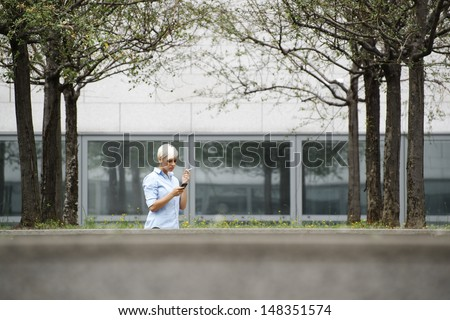 young businesswoman smoking cigarette during break out of office building. Wide shot, copy space - stock photo