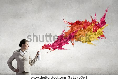 Young businesswoman spraying colorful paint from balloon